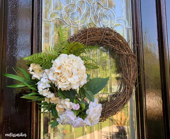 grapevine wreath with faux fern and flowers on wooden door with glass window
