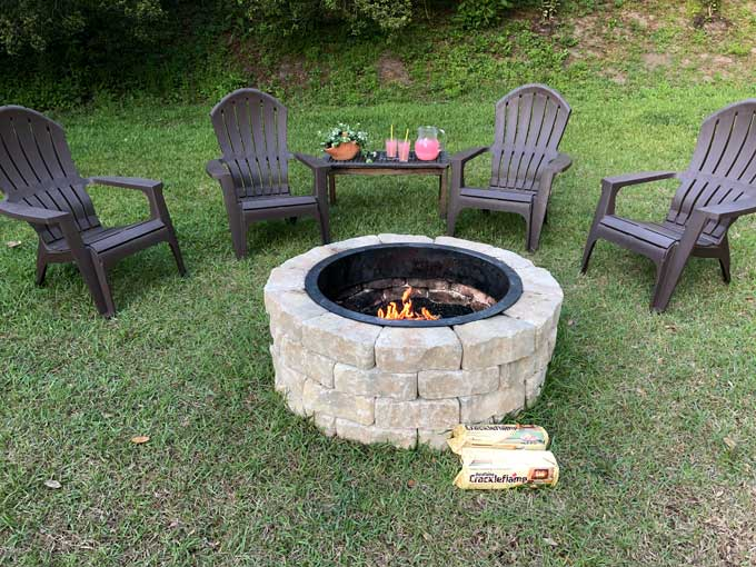 Adirondack chairs near stone fire pit and lemonade pitcher and glasses on table in background