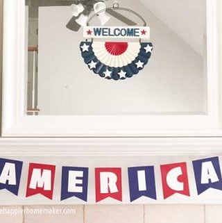 banner spelling America in red white and blue on white mantel with mirror over it
