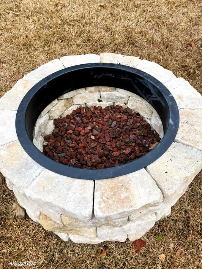 stone fire pit viewed from above with lava rock in the center
