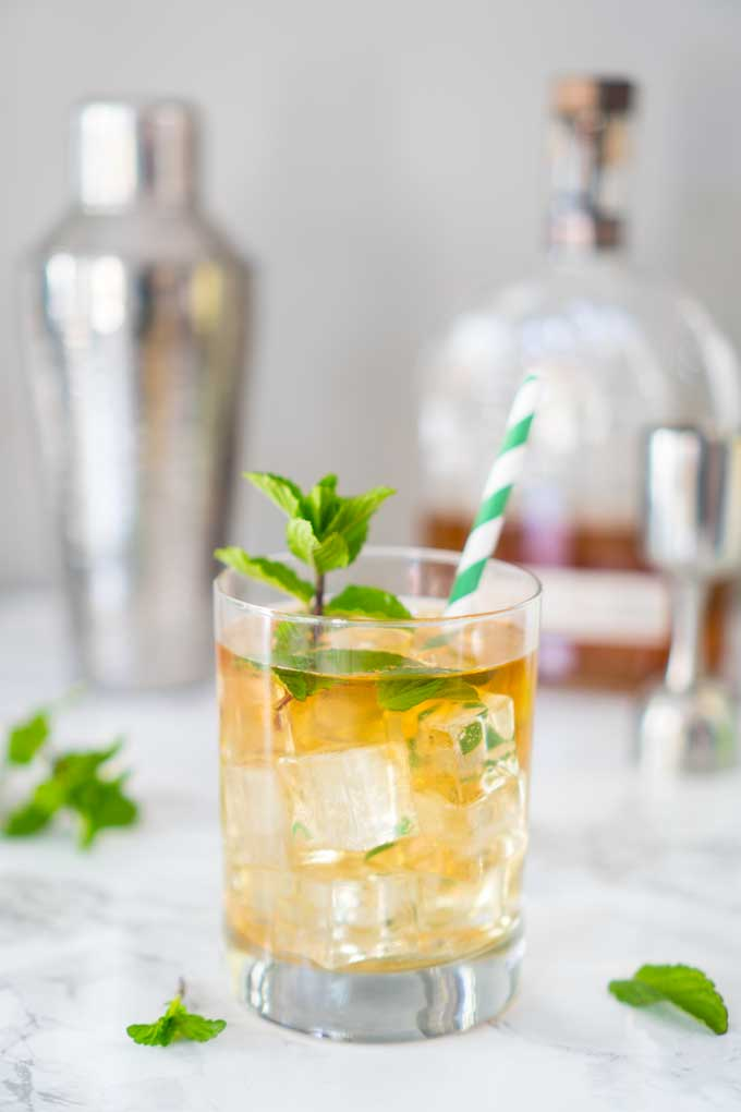 Mint julep in glass with green and white striped straw and mint sprig garnish