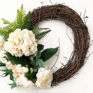 grapevine wreath with fake ferns and white flowers