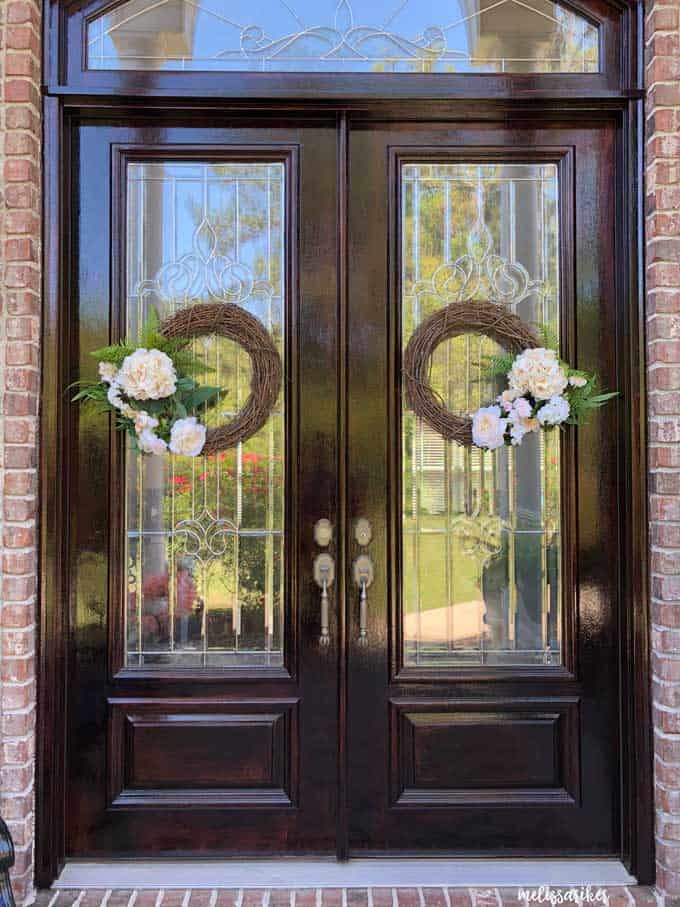 large double wooden doors with two grapevine wreaths with fake ferns and white flowers
