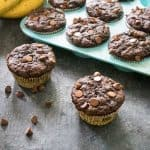 chocolate zucchini muffins in blue silicone baking tray with two muffins in front and chocolate chips scattered on table