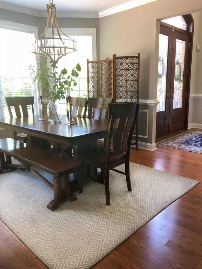 A dining room table with wood screen in background