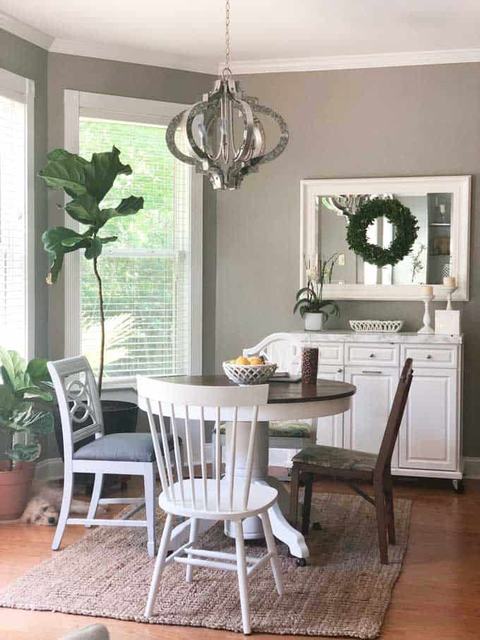 A dining room table with mismatched chairs and modern light fixture