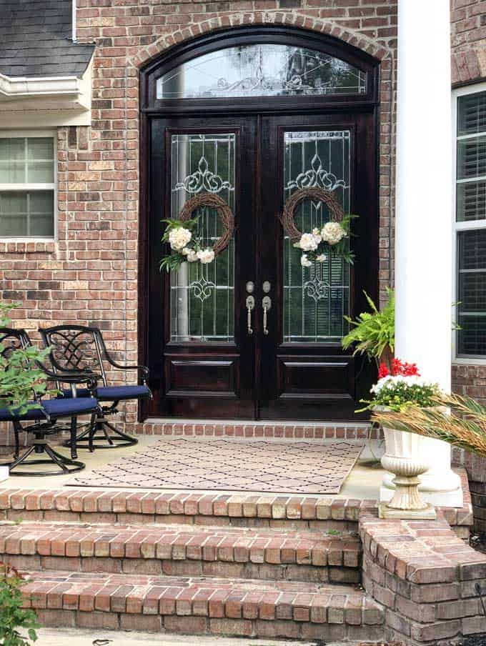 large double wood doors on brick home with matching wreaths