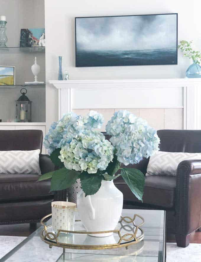 A living room filled with furniture and vase of blue hydrangeas on a table