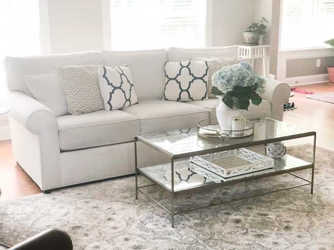 A living room filled with white couch and gold and glass coffee tables