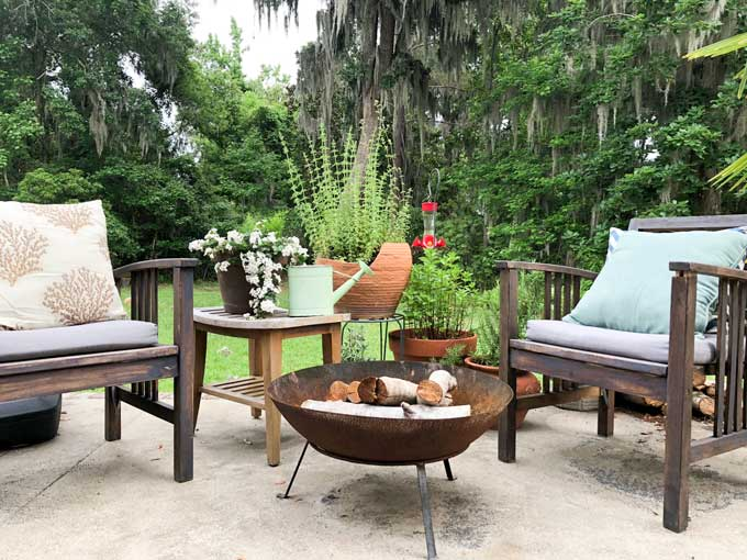 metal fire pit with wood chairs and plants on outdoor patio
