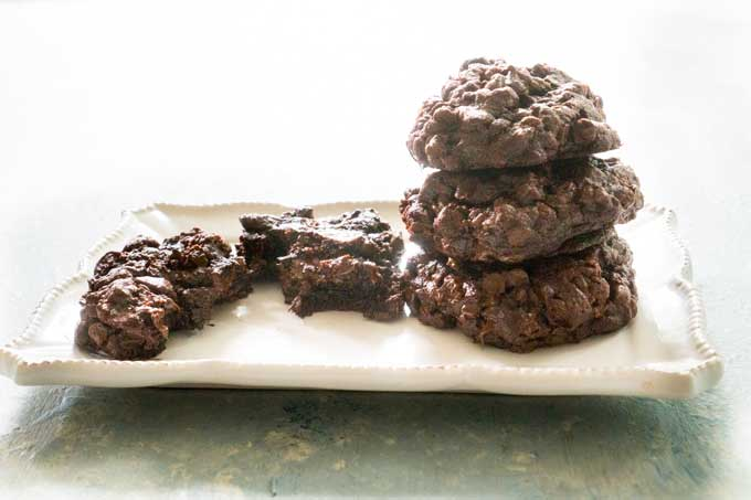 chocolate cookies stacked on white plate with one next to them broken in half