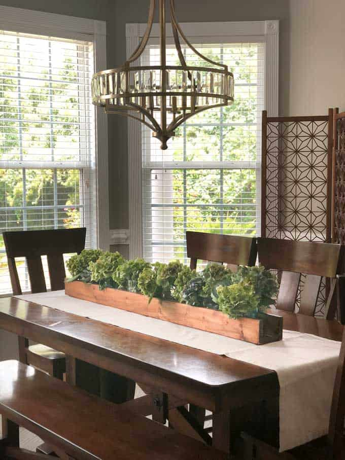 dining room with wood table with white runner and wooden trough holding dried hydrangeas