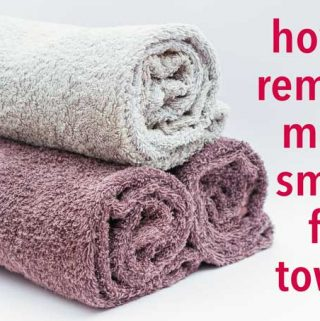 stack of folded towels with text reading how to remove musty smell from towels mildew smelly