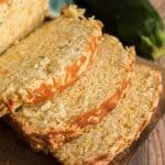 close up of sliced cheddar zucchini bread with whole zucchini next to it
