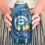 hands holding bottle of blue Dawn dish soap