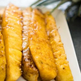 close up of brown sugar grilled pineapple spears on white plate
