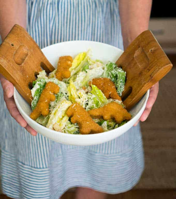hands holding white bowl with wood salad servers and caesar salad and dinosaur shaped chicken nuggets