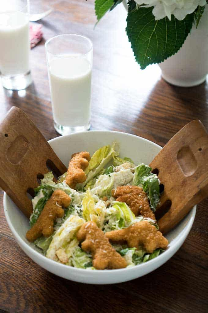 white bowl with wood salad servers filled with caesar salad and dinosaur shaped chicken nuggets