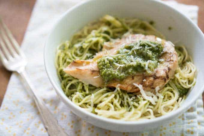 chicken breast on angel hair pasta with pesto in white bowl