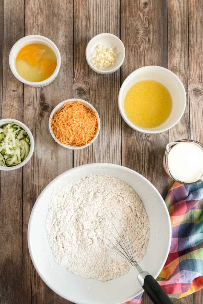 overhead photo of ingredients for cheddar zucchini bread in white bowls on wood plank background