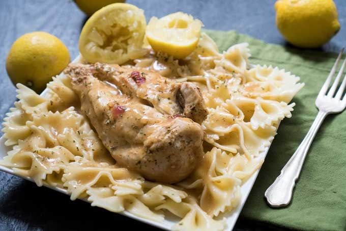 lemon chicken breast on bowtie noodles with squeezed lemons in background