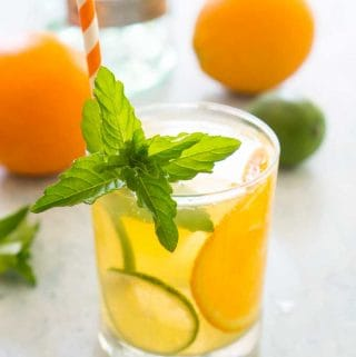 glass of orange mojito with mint garnish and orange and white striped straw