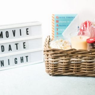 A close up of a basket with gifts and a letter board saying movie date night