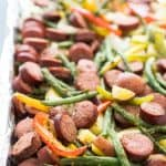 A close up of sausage and veggies on baking sheet