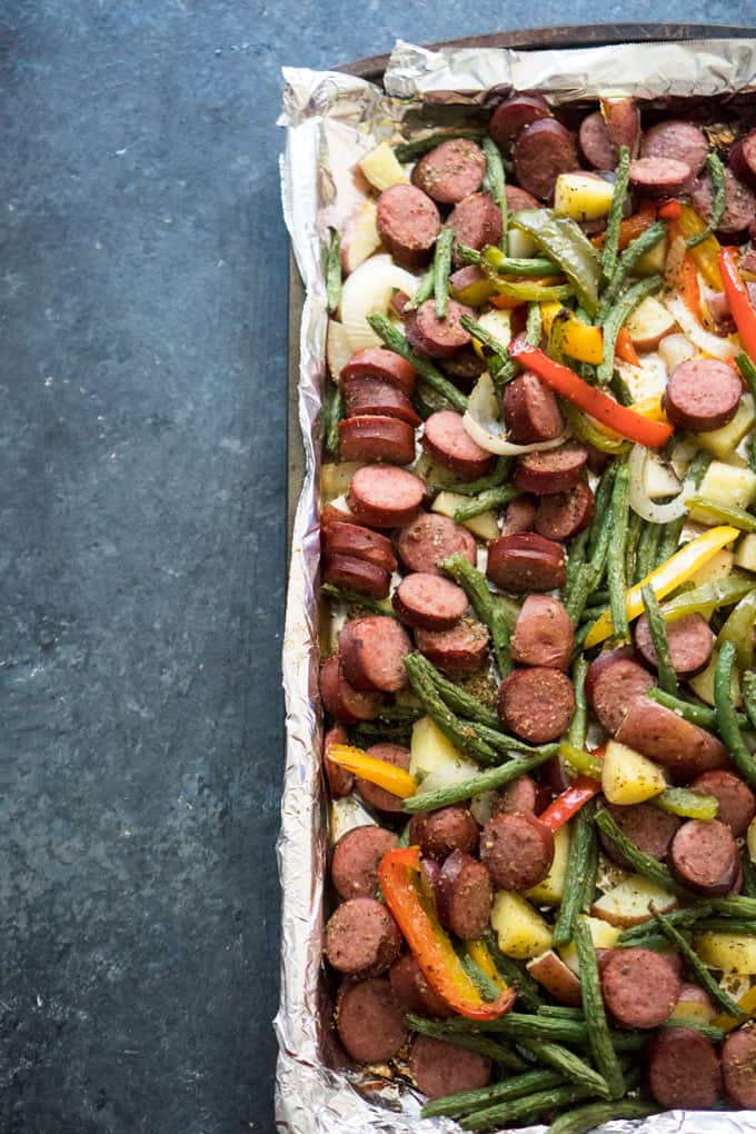 overhead view of sausage and chopped vegetables on foil elined baking dish