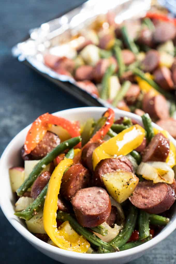 Sheet pan sausage and vegetables in white bowl