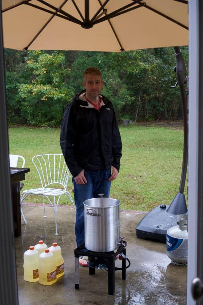 A tall man standing behind a silver turkey fryer