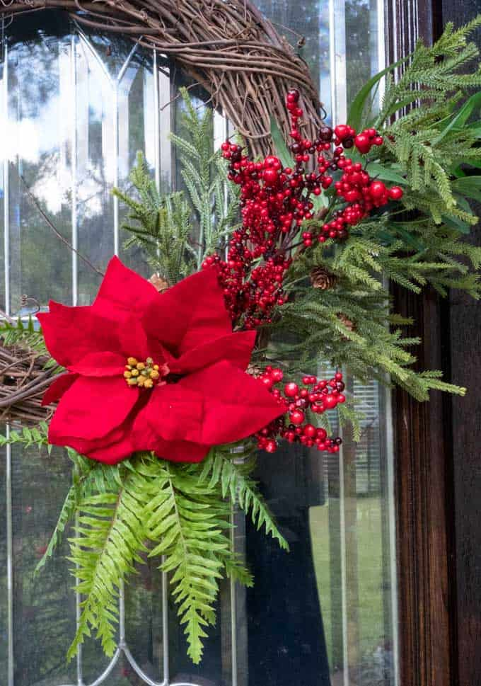 close up of wreath with red flower and greenery