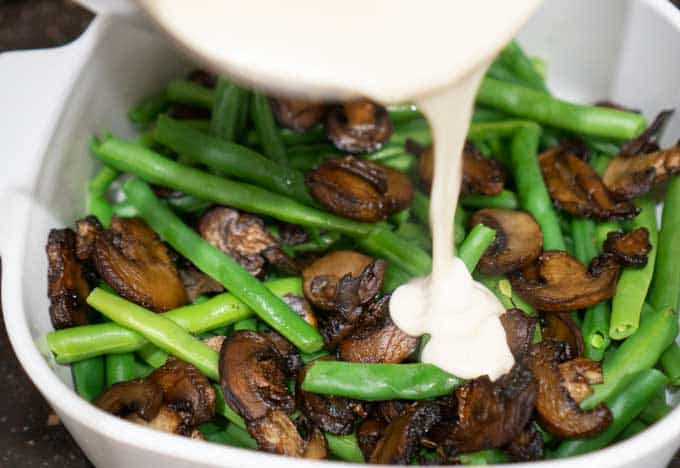 pouring bechamel sauce over green beans and mushrooms to make green bean casserole from scratch