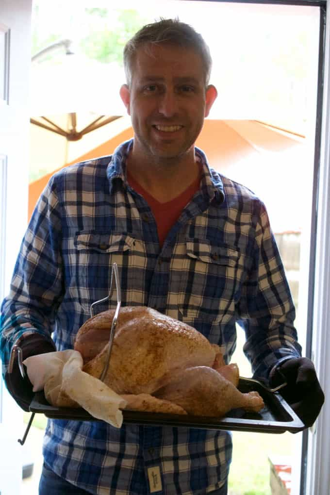 A tall man standing in front of a window holding a cooked turkey