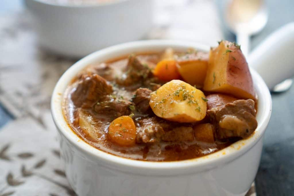 A close up of a white bowl with beef stew