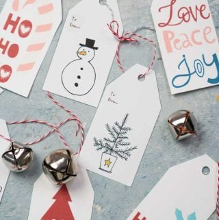 overhead view of free printable Christmas gift tags with small bells and pom pom ribbon