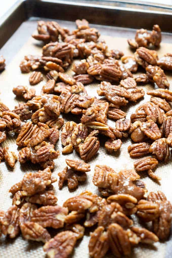 Spicy Candied Pecans on baking sheet with silicone mat