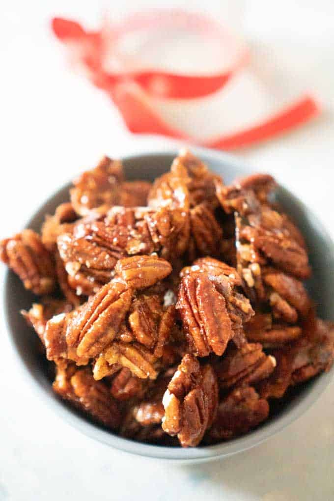 Spicy Candied Pecans close up in bowl with ribbon in background