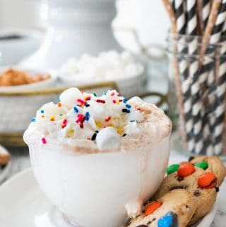 hot chocolate in white mug with whipped cream, marshmallows, and sprinkles on top with cookies on saucer below