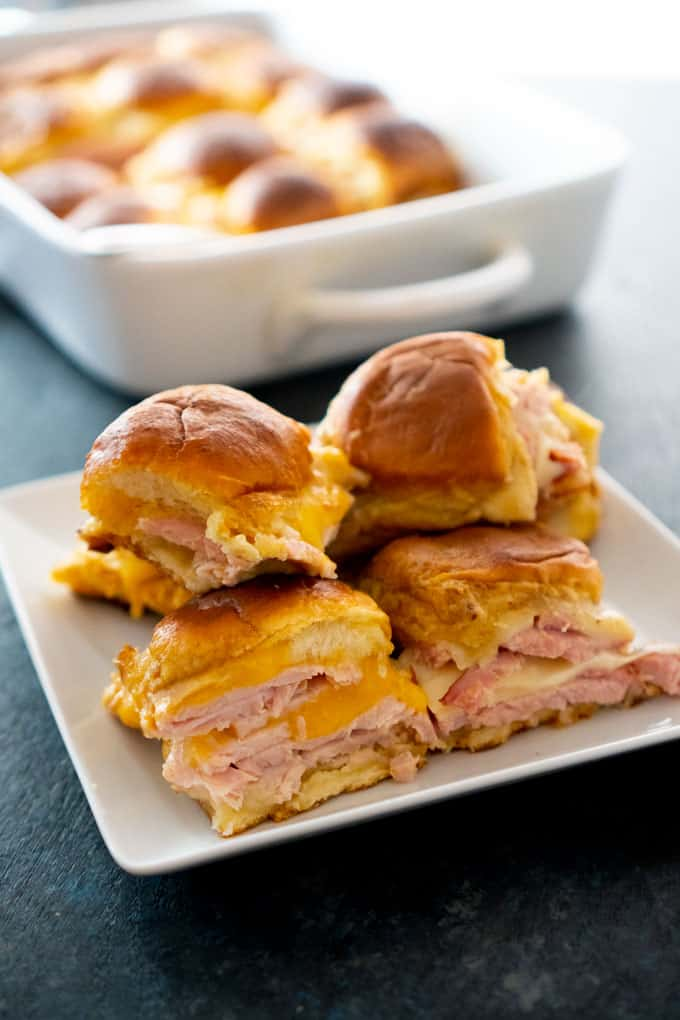 Ham & Turkey Hawaiian Roll Sliders on white square plate in front of white casserole dish