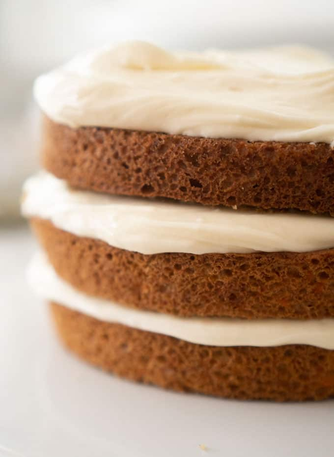cream cheese frosting in between layers of carrot cake