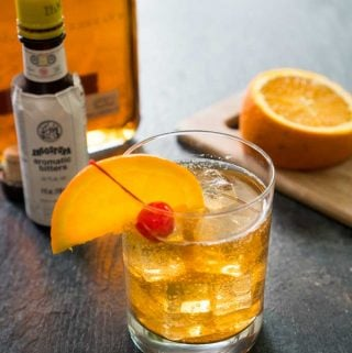 old fashioned bourbon cocktail with orange slice and cherry in front of bottle of bitters and sliced orange on cutting board