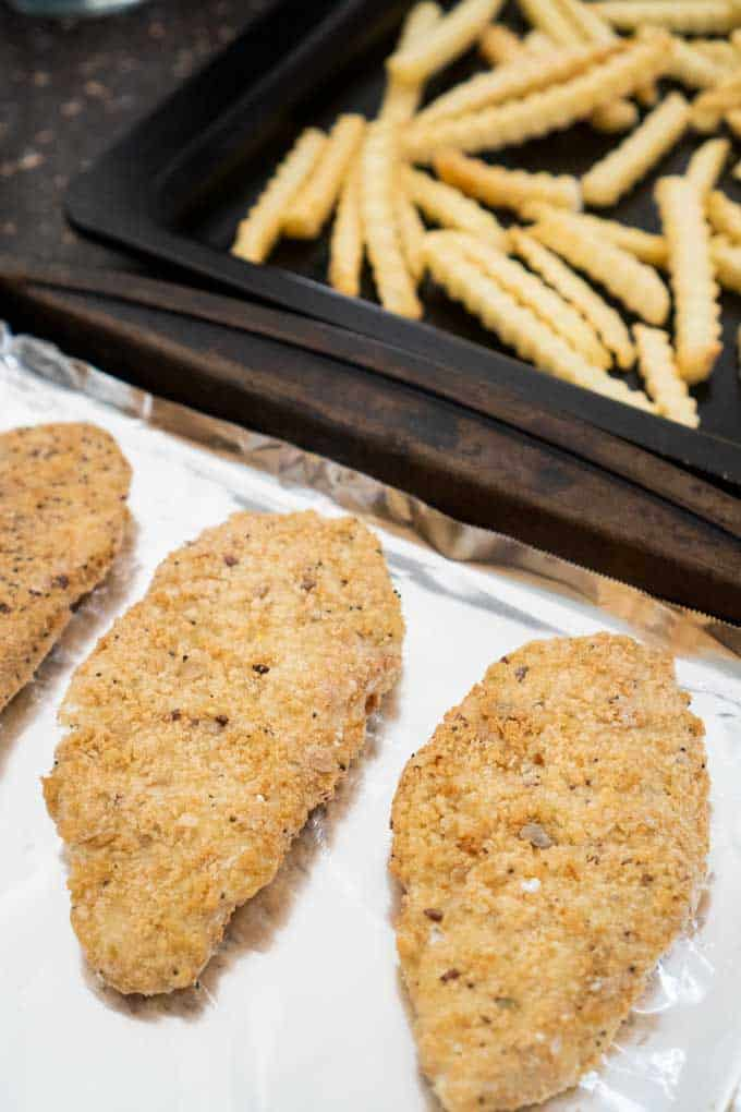 cod fillets and french fries on baking sheet