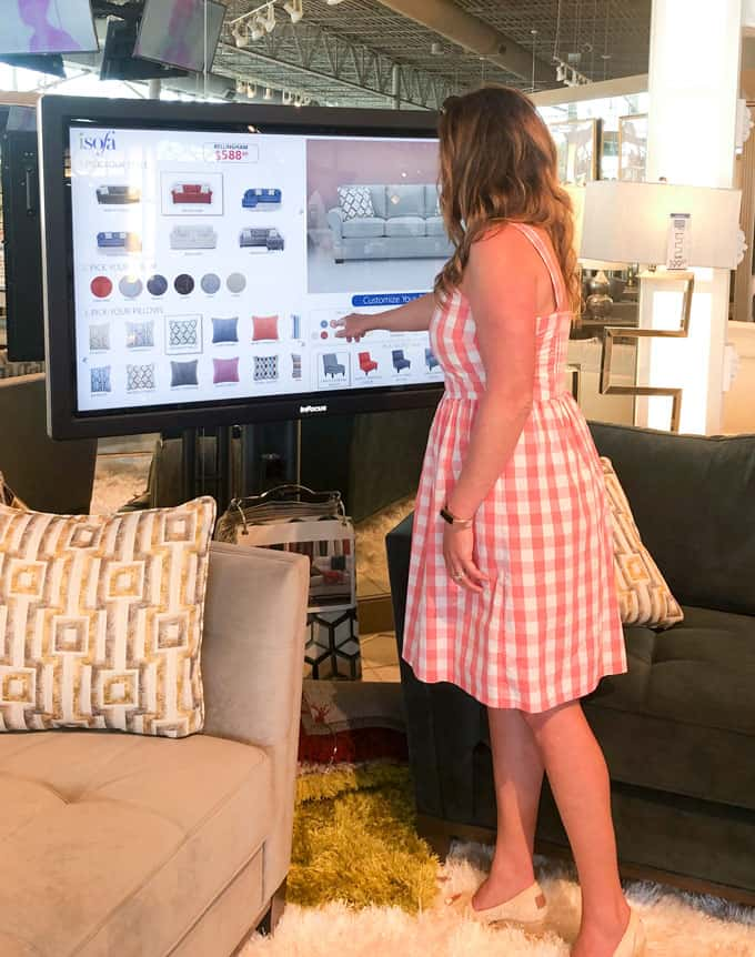 woman standing in front of touch screen isofa design center at rooms to go