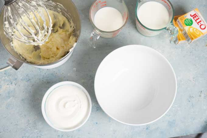 overhead view of stand mixer glass and measuring cups full of milk container whipped cream pudding mix