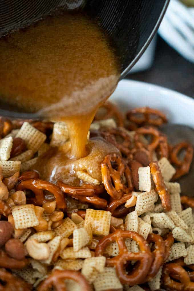 pouring toffee mixture over snack mix with pretzels chex cereal nuts