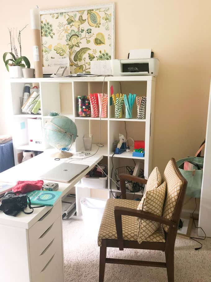 cluttered office with white cube styleb ook shelves and white ikea desk and midcentury vintage chair