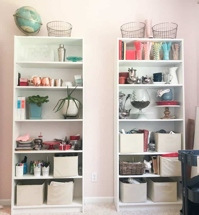 two white bookshelves with colorful craft supplies and photography props
