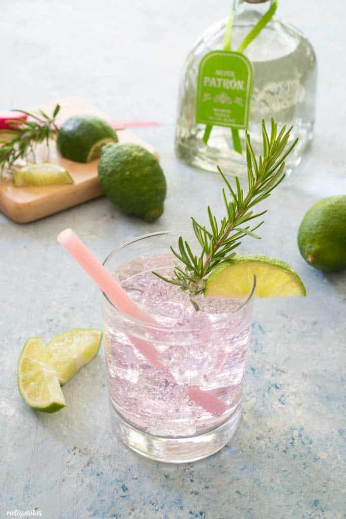 paloma cocktail in short glass garnished with lime slice and rosemary in front of tequila bottle and limes