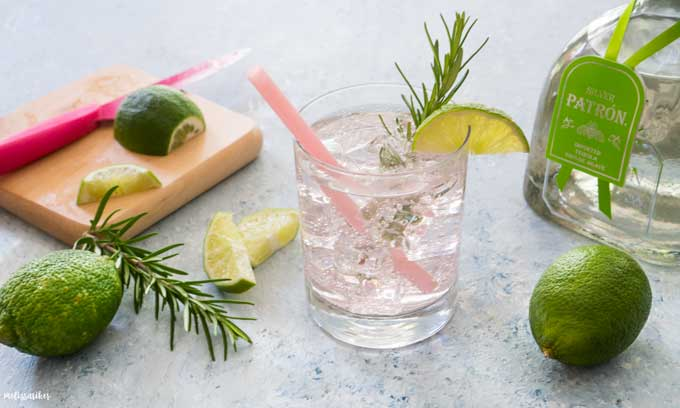 close up of paloma cocktail garnished with lime and rosemary with pink straw